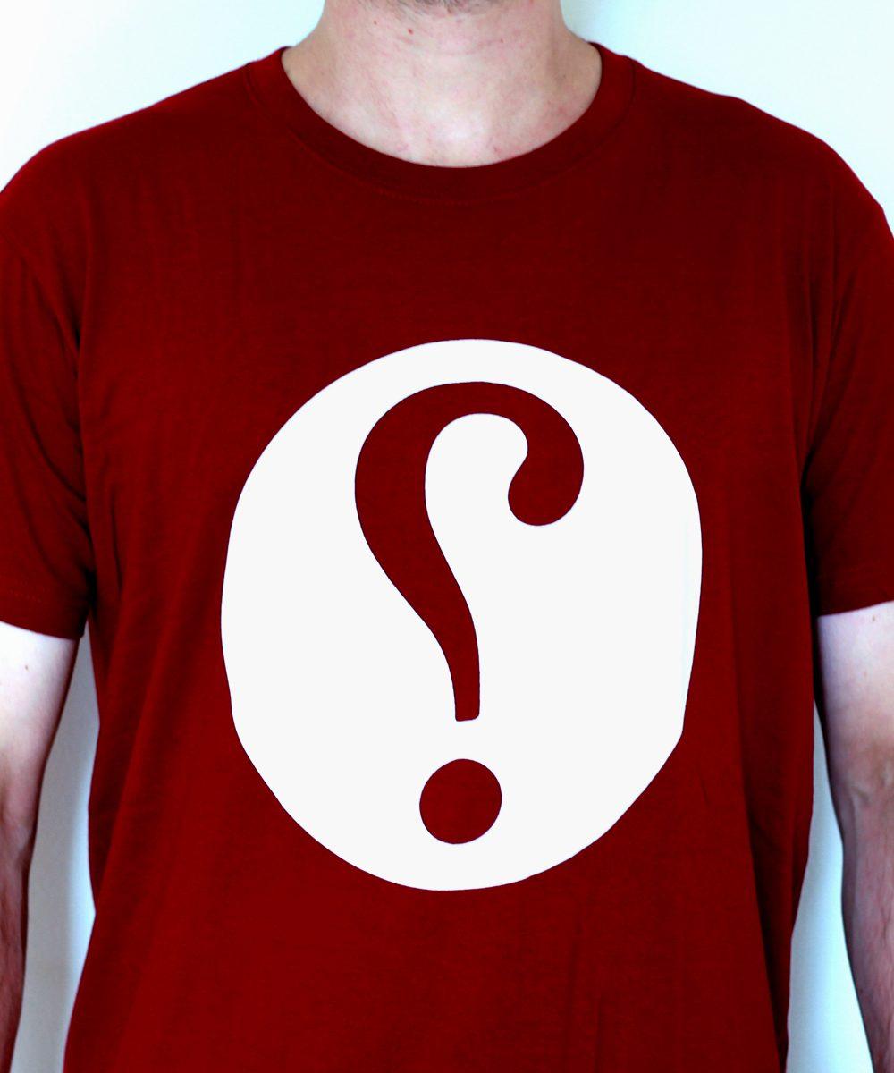 Shirt mit Ironiezeichen auf rotem Stoff.